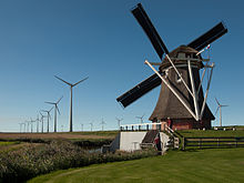 Turbines in the backgound of a Windmill. Image courtesy of Wikipedia.