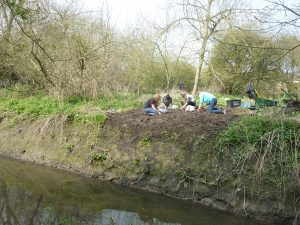Volunteers working to improve the banks of the becks at St Nicks