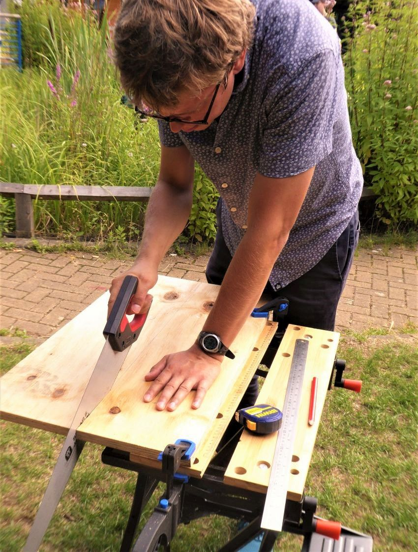 Woodworking participant sawing on workbench