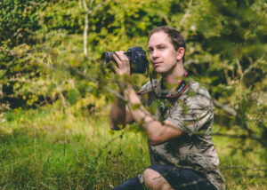 Photograph of Ecotherapy tutor Phil Taylor looking through his wildlife camera