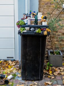An overflowing wheelie bin full of all types of material