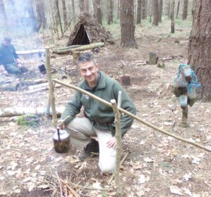 Ecotherapy Bushcraft tutor Andrew Garner making tea on an open fire in the woods