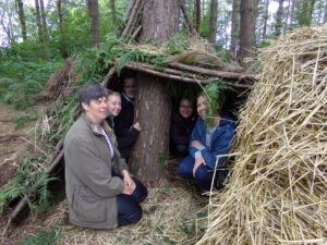 Young people inside a shelter they constructed at the St Nicks Bushcraft course