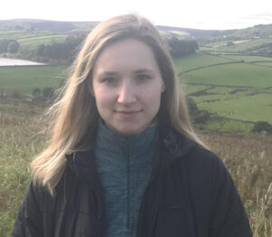 Natalie Rea, St Nicks Volunteer. Young woman with light hair standing in a green landscape.