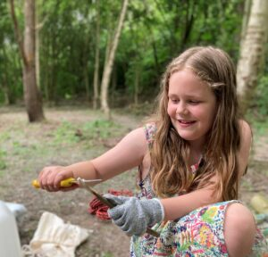 Child outside using a knife to whittle a stick