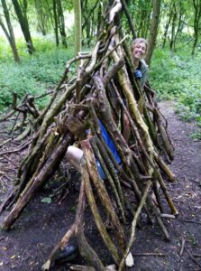 a den made of branches in the woods with a couple of people inside